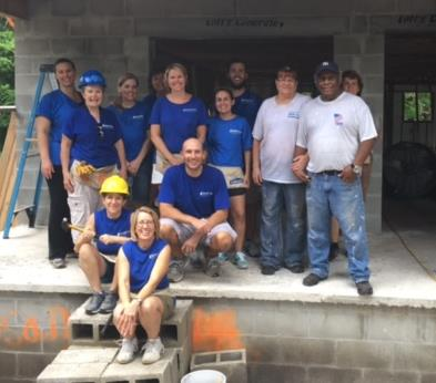 (Seminole employees and family members, in blue shirts, alongside homeowners Rhea and Melvin Robinson.)